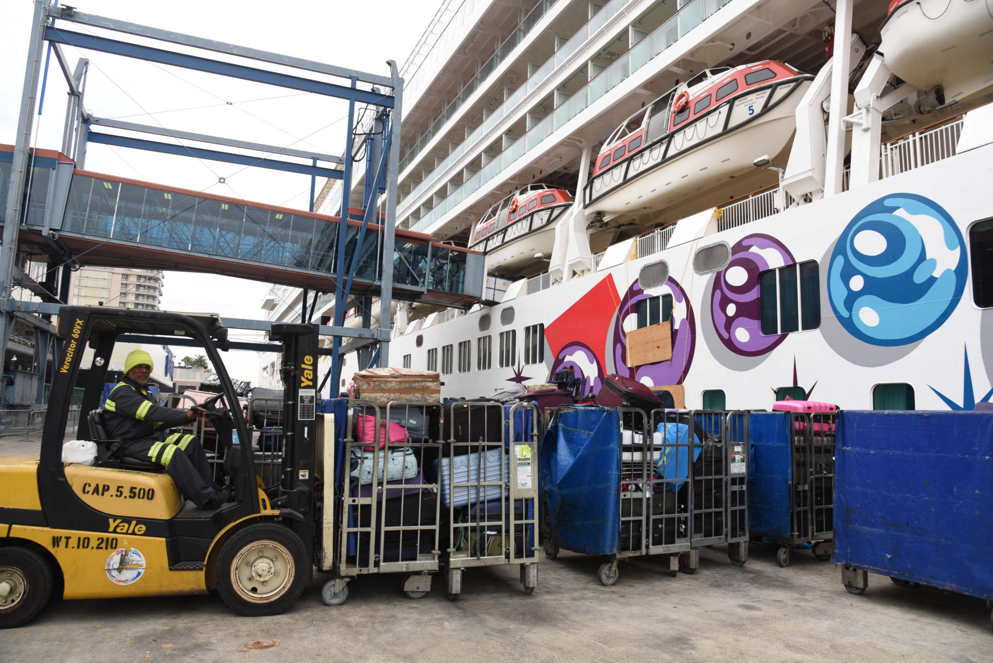 Worker Loads Passenger Luggage on Norwegian Pearl